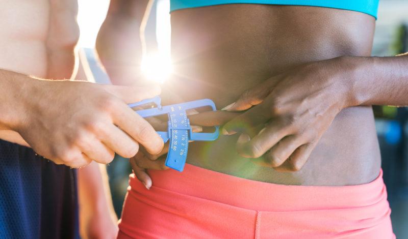 Trainer misst das Körperfett einer sportlichen Frau mit einem Messschieber.